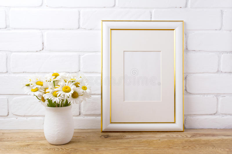 Gold decorated frame mockup with chamomile bouquet in rustic vase stock images