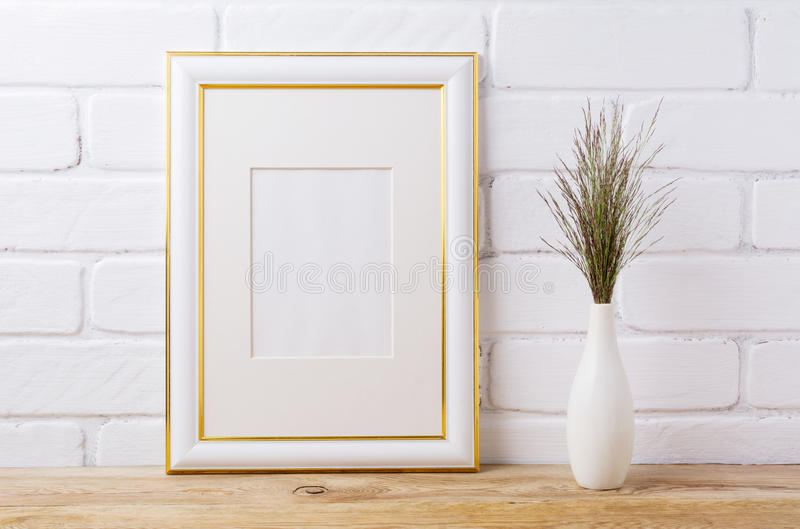 Gold decorated frame mockup with dark grass in elegant vase royalty free stock photo