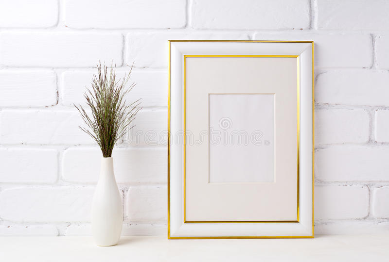 Gold decorated frame mockup with dark grass in vase near brick w stock image