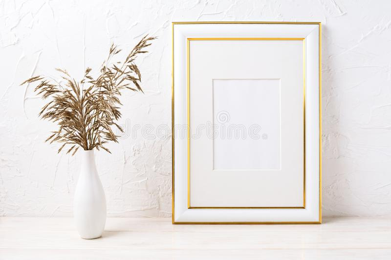 Gold decorated frame mockup with dried grass. Gold decorated frame mockup with decorative dried grass. Empty frame mock up for presentation artwork. Template stock photo