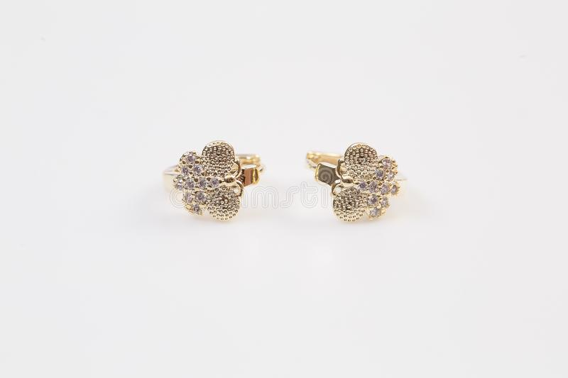 Gold decorative diamond butterfly earrings on the white background. Gold decorative diamond butterfly earrings o stock images