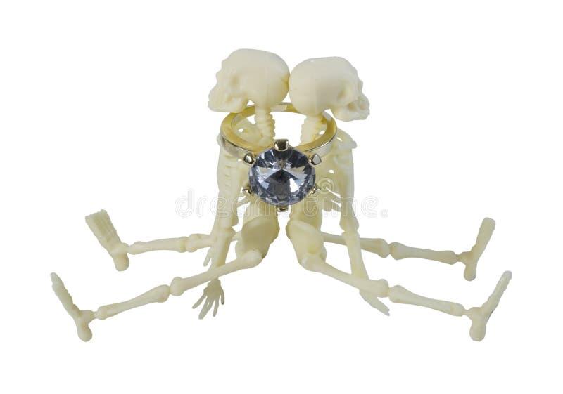 Gold diamond engagement ring around two Skeletons stock photos