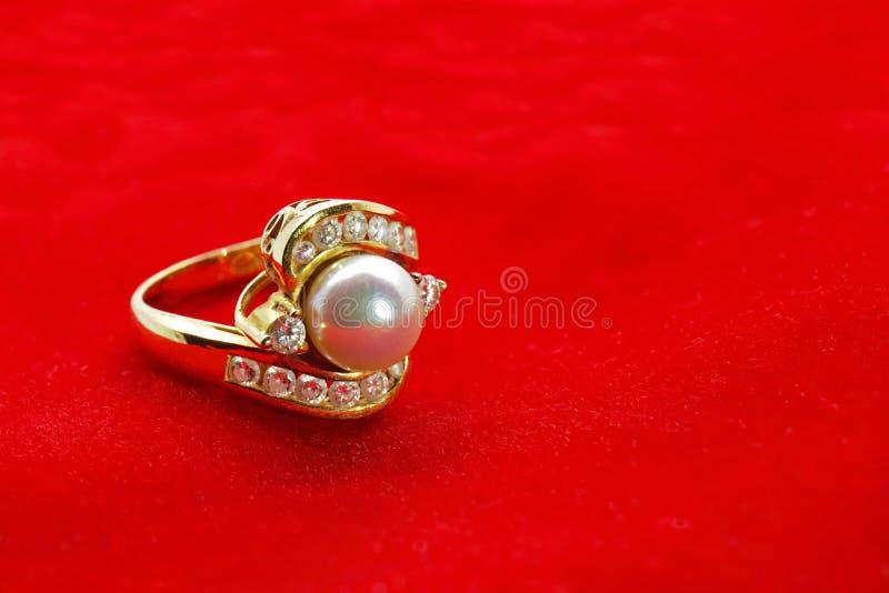 Gold Diamond Pearl Ring on Red Velvet royalty free stock image