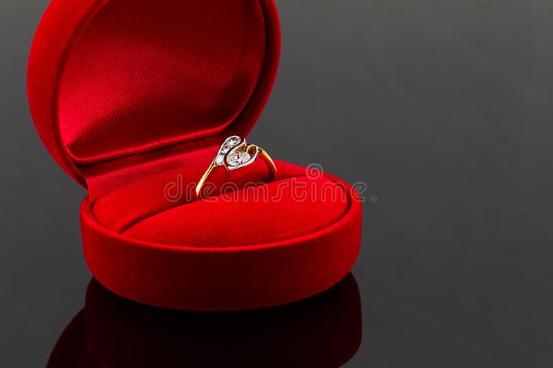 Gold diamond ring in red heart shaped velvet box on dark glossy stock photography
