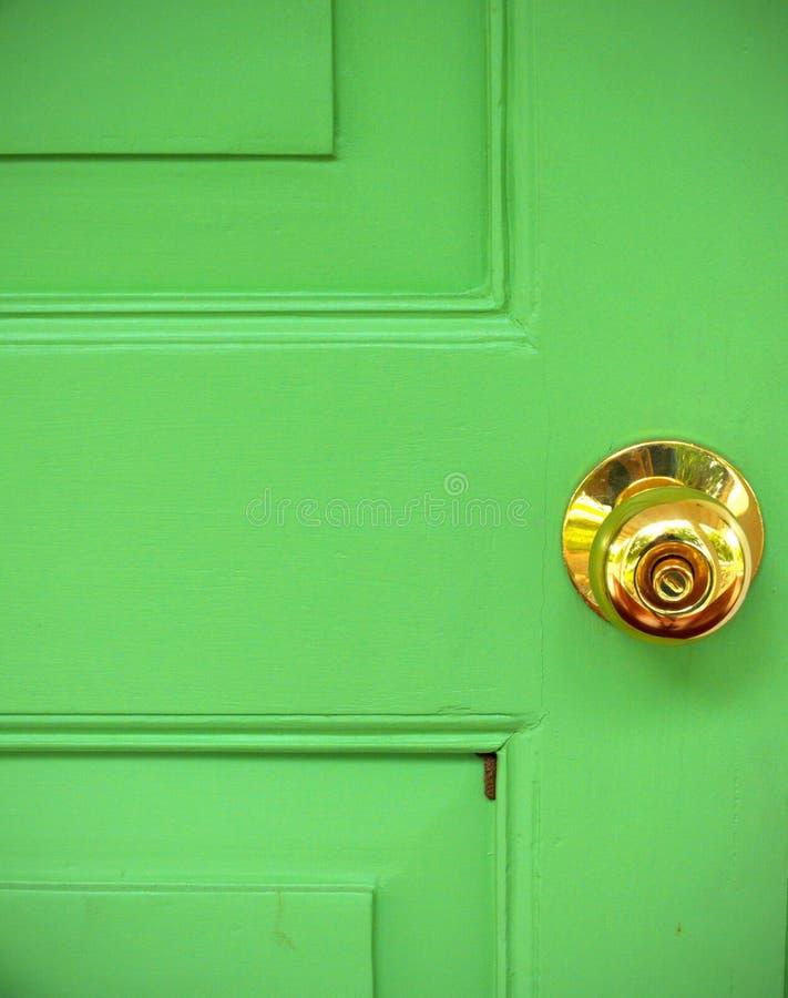 Gold door knob on green. Close up gold door knob on green stock photo