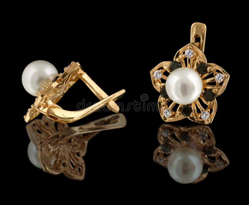 Gold earrings with diamonds and pearl royalty free stock photo