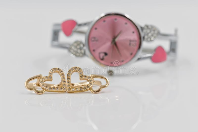 Gold earrings in the shape of a heart on a background of elegant royalty free stock image