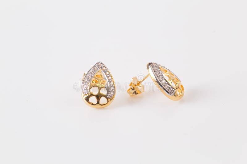 Gold earrings stud with diamonds macro shot on the white background 4 stock photography