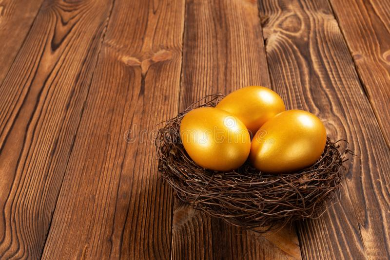 Gold eggs on nest on wooden background royalty free stock images