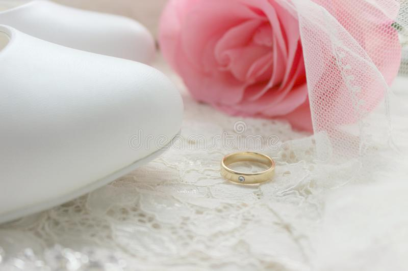 Gold engagement ring.White shoes. wedding shoes. Bride`s high heels. The fees of the bride. Wedding jewelry. stock photo