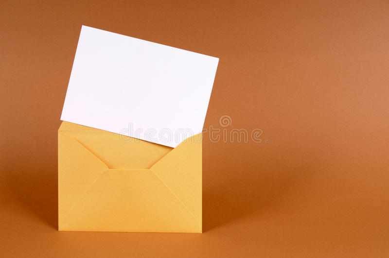 Envelope with blank letter or message card, copy space. Gold envelope with blank message card letter or invitation isolated on a brown background. Space for copy stock photos