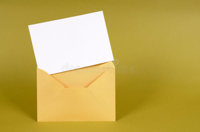 Gold brown manila envelope with blank message card or letter, copy space. Metallic gold envelope with blank message card letter or invitation isolated on a green stock photo