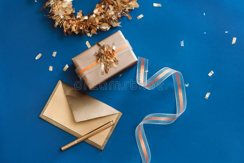 Gold Envelope, Box, Ribbon with wreath made of Christmas decoration on blue background.  stock images