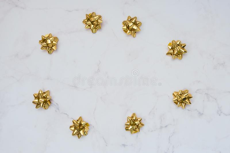 Gold festive bows on white marble background. Backdrop for cards, invitations, greetings.  stock photos