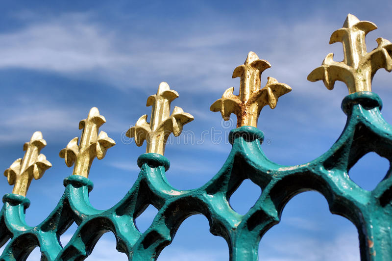 Gold Fleur de Lis auf blauen Eisengeländern lizenzfreies stockbild