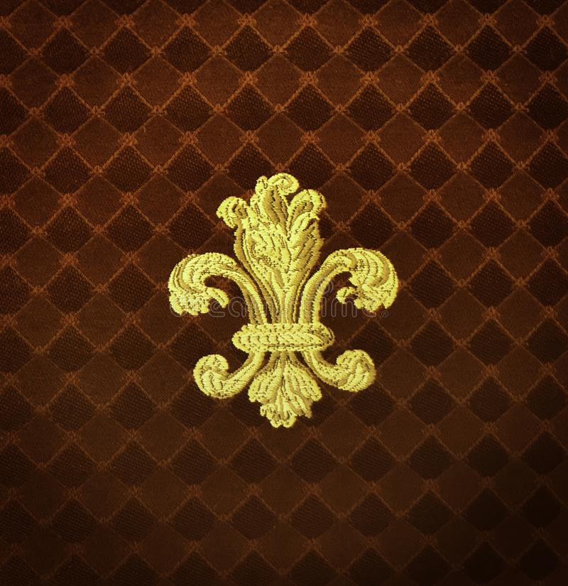 Gold Fleur-de-lis embroidered on a rust color fabric. With a slight vignette royalty free stock photo