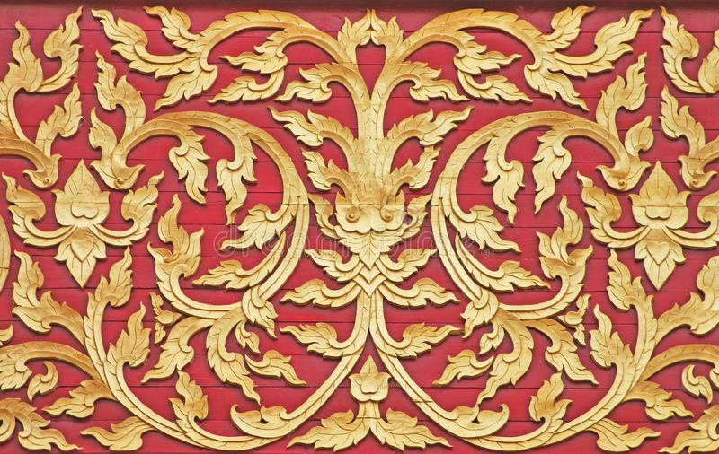 Gold flower patterns on red wooden wall background at temple royalty free stock images