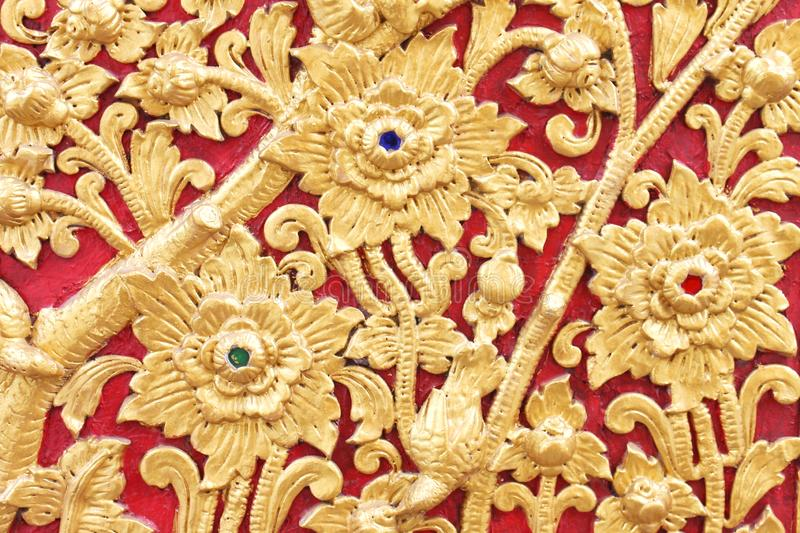Gold flower patterns on red wooden wall background at temple royalty free stock photo