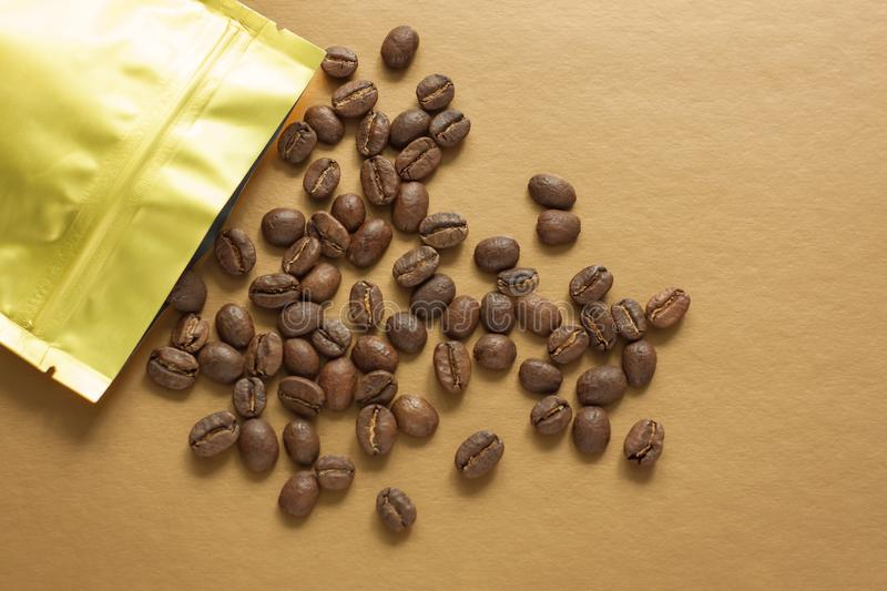 Gold foil bag with coffee beans on golden background. Packaging template mockup. Aluminium package for tea, flatlay. stock image