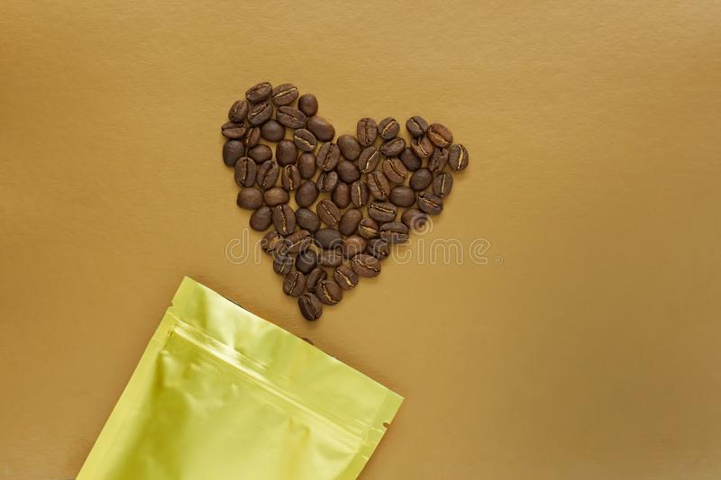 Gold foil bag with coffee beans on golden background. Packaging template mockup. Aluminium package for tea, flatlay stock photos