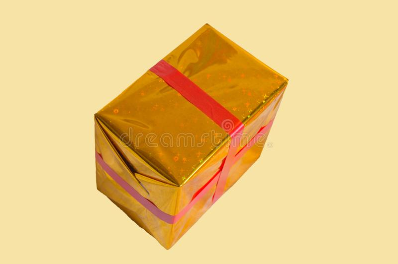 Gold foil wrapped gift box with red ribbon isolated on yellow background stock image