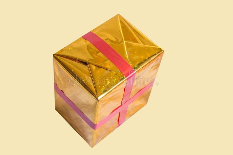 Gold foil wrapped gift box with red ribbon isolated on yellow background royalty free stock images