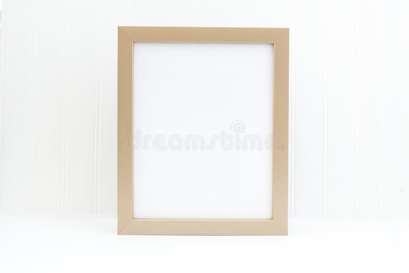 Gold frame mockup. Empty frame mockup on white. Simple empty gold frame mockup. This is a 8x10 frame against a white wall. With bead-board background. Minimalist stock illustration