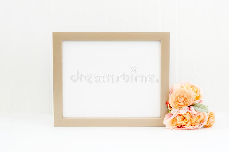 Gold frame mockup. Landscape empty frame mockup on white background with flowers. Simple empty gold frame mockup. This is a 8x10 frame against a white wall stock illustration
