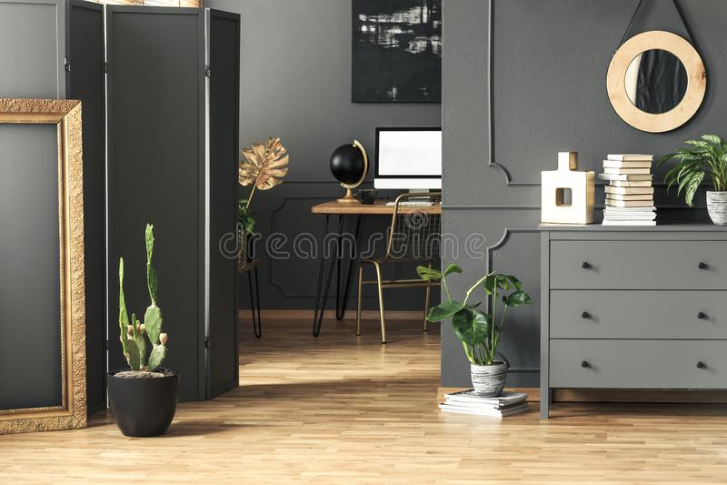 Gold frame next to cactus in grey workspace interior with round mirror above cabinet. Real photo stock image