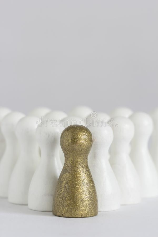Gold gamefigurine ahead of white ones, signalling winning and leadership stock photo
