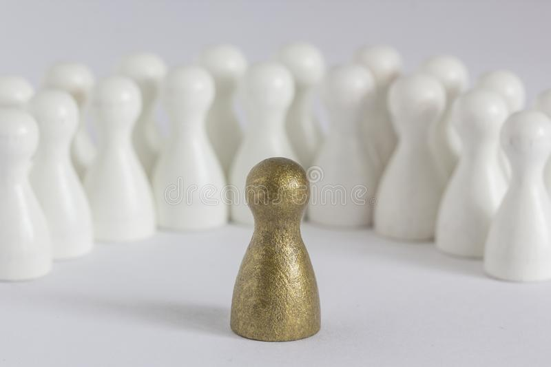 Gold gamefigurine ahead of white ones, signalling winning and leadership stock photography