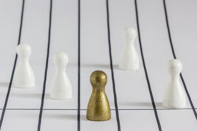 Gold gamefigurine ahead of white ones, signalling winning and leadership royalty free stock image