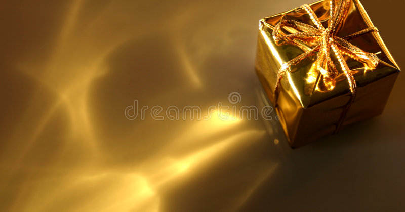 Gold Gift Abstract. This is a small shiny gold gift box with gold yellow cast off reflections. Abstract with shallow depth of field. Room for text and would be royalty free stock image