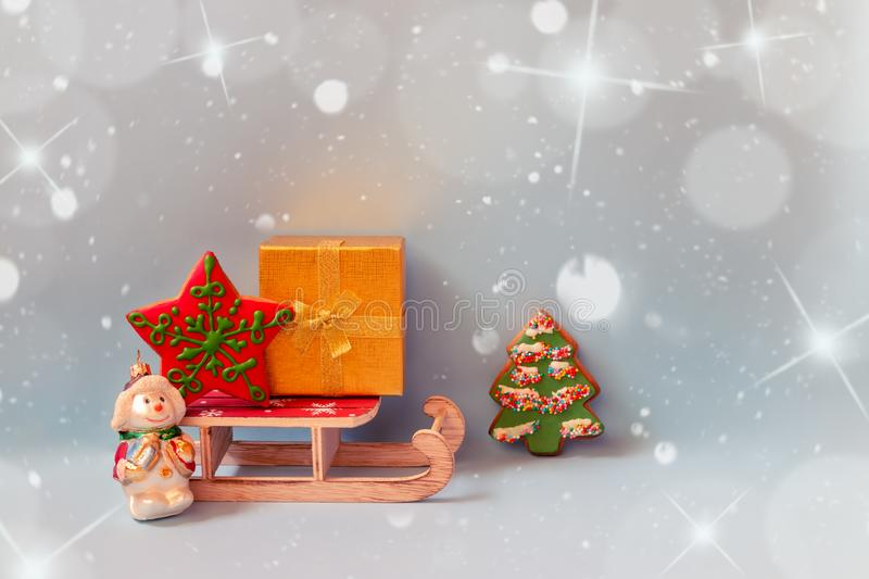 Gold gift box,  gingerbread cookies, wooden sledge and christmas decoration snowman on blue background. Holiday mood. View with copy space royalty free stock images