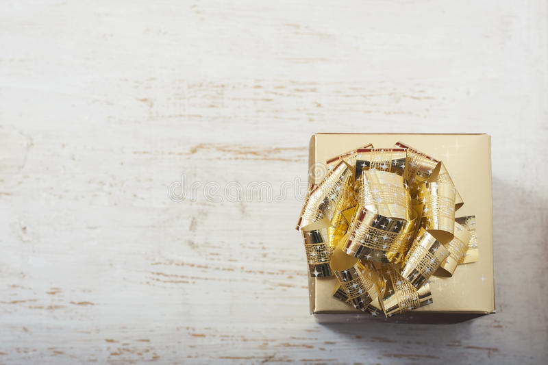 Gold gift box on white table. Selective focus royalty free stock images