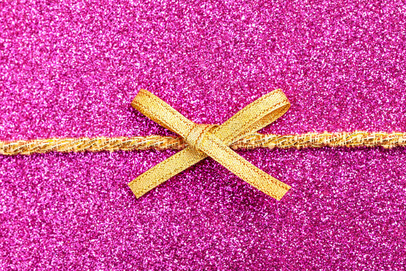 Gold gift ribbon bow. On purple shiny background royalty free stock images