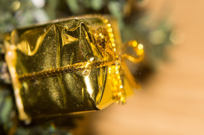 Gold Giftbox Toy. Christmas decoration, golden gift box toy on branch royalty free stock images