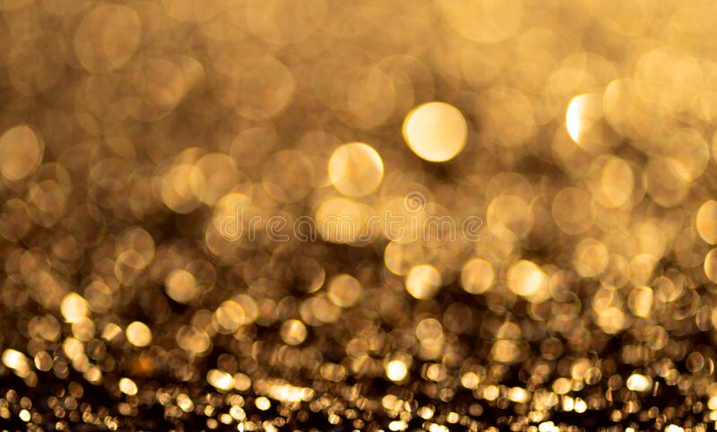 Gold glitter particles background. Sparkling light boke blur. Template for christmas theme royalty free stock photography