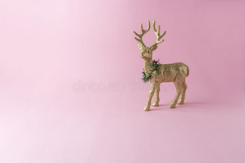 Gold glitter reindeer on pink background. Minimal New Year royalty free stock image