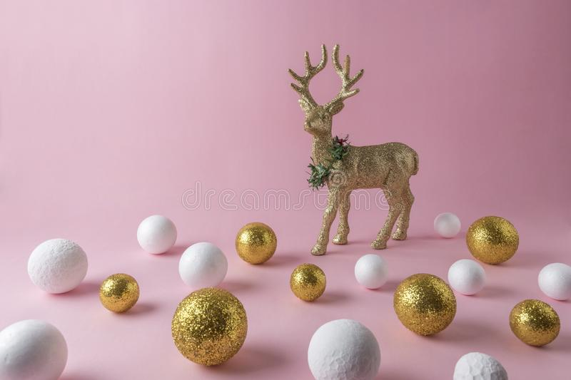 Gold glitter reindeer with gold and white glitter ball decoration on pink background. Minimal New Year composition royalty free stock photo