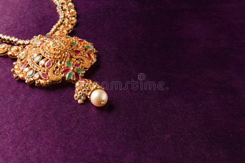 Gold Guttapusalu Necklace mit Edelsteinen ein traditioneller indischer Hochzeitsschmuck auf blauem textilen Hintergrund stockfoto