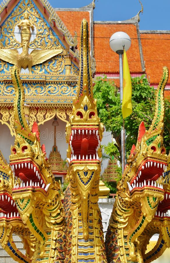Gold half snake, half-dragons decorating Naga staircase to Sangharam Wat Wichit, Phuket, Thailand. Gold half-snake, half-dragons decorating Naga staircase to royalty free stock photo