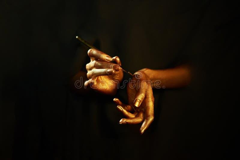 Gold-Hand-witn Bürste lokalisiert auf schwarzem Hintergrund lizenzfreie stockbilder