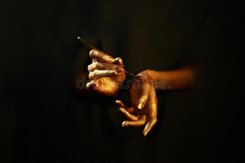 Gold hands witn brush isolated on black background royalty free stock images