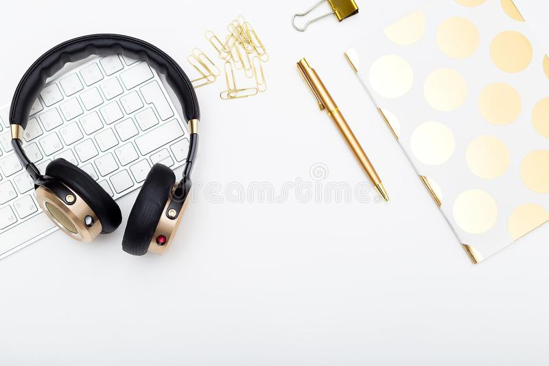 Gold headphones and keyboard on white background. Flat lay stock images