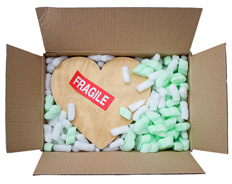 Gold heart in box with fragile sticker. Fragile heart, gold heart with fragile sticker inside box full of protective foam packaging isolated on white royalty free stock photos