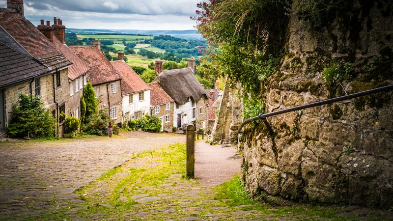 Famous Gold Hill cobbled street with thatched roof houses in Shaftesbury, UK. Gold Hill in Shaftesbury is an authentic place in the South of the UK. View of a royalty free stock photos