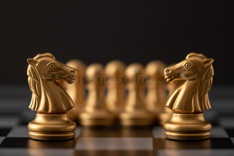 Gold horse of the chess. In the game on board, battle, bishop, business, castle, challenge, checkmate, chessboard, choose, competition, concept, defeat, fight royalty free stock photography