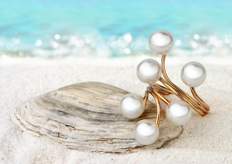 Gold Jewellery ring with pearls on sand beach background, soft f royalty free stock photos