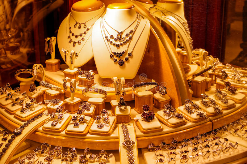 Gold jewellery in a shop window royalty free stock photography